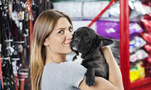 Portrait of loving mid adult woman kissing French Bulldog at pet store